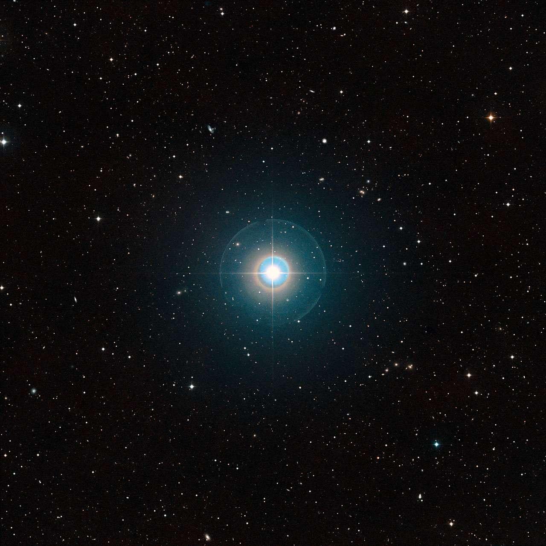 Cette image à grand champ du ciel autour de Tau Bootis a été créée à partir de clichés du Digitized Sky Survey 2. L'étoile elle-même, suffisamment brillante pour être vue à l'œil nu, se trouve au centre. Les traits fins et les cercles colorés autour d'elle sont des artefacts provoqués par le télescope et la plaque photographique utilisée et ne sont pas réels. L'exoplanète Tau Bootis b est en orbite à faible distance de l'étoile et est totalement invisible sur cette image. La planète vient juste d'être détectée de manière directe grâce à sa propre lumière en utilisant le VLT de l'ESO. © ESO/Digitized Sky Survey 2