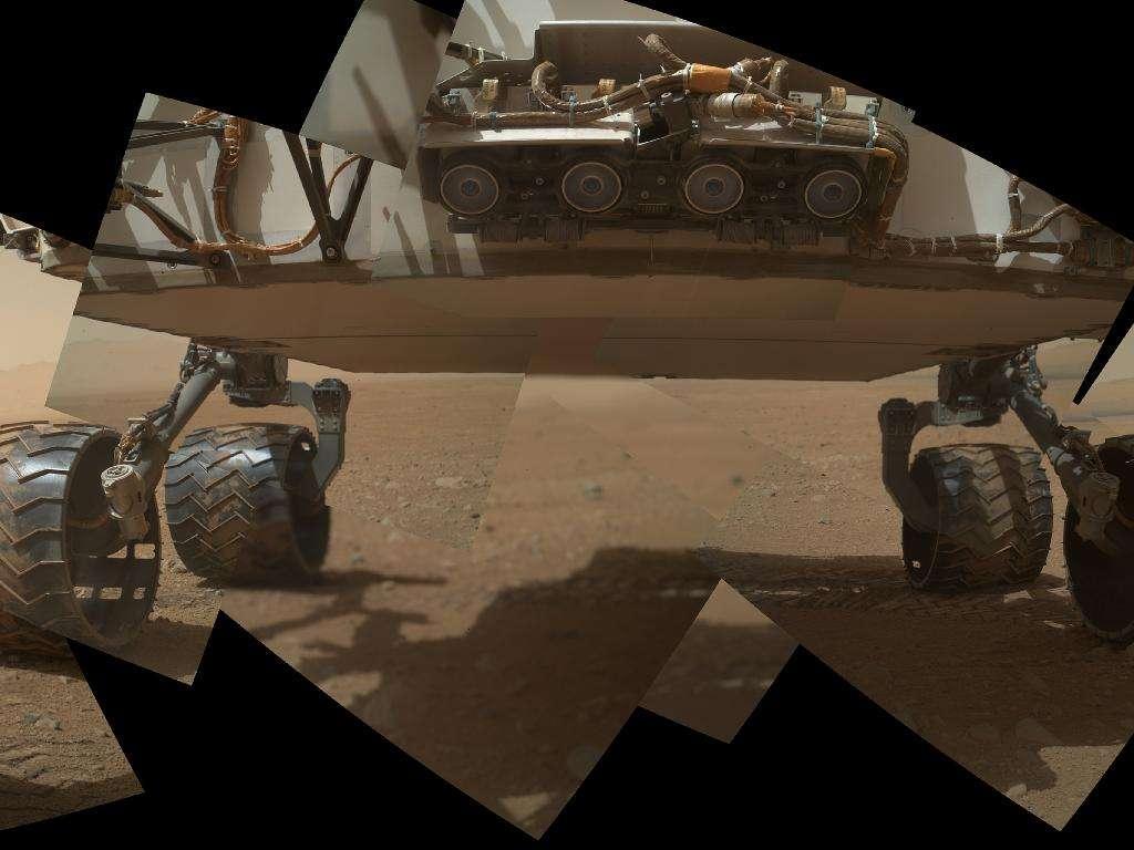 Mosaïque de photographies saisies le 9 septembre 2012 par la caméra Mahli (Mars Hand Lens Imager), fixée au bout du bras articulé du rover. Les quatre cercles au premier plan sont les Hazcam (Hazard-Avoidance cameras). Verticalement, environ 60 centimètres séparent le sol martien du châssis de Curiosity. © Nasa/JPL-Caltech/Malin Space Science Systems