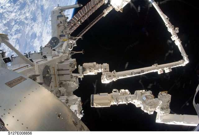 Une partie de la plate-forme des expériences extérieures du module Kibo (Japanese Experiment Module - Exposed Facility). Le Canadarm, bras robotisé de l'ISS, manœuvré ici par la Canadienne Julie Payette, est bien visible. Le plus petit, à droite, est celui de la navette Endeavour. L'image est prise de l'intérieur de Kibo. © Nasa