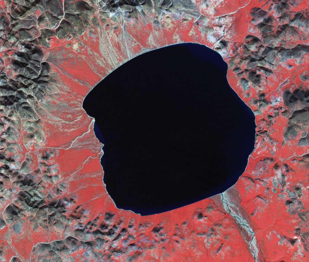 Image du lac russe El'gygytgyn (couleurs non réelles), qui se situe environ 100 km au nord du cercle polaire arctique. Le cliché a été pris le 18 août 2008 par le capteur Aster (pour Advanced Spaceborne Thermal Emission and Reflection Radiometer) embarqué sur le satellite Terra. Le rouge et le brun-gris indiquent respectivement la présence de végétation ou de terres nues. La tache au centre correspond au lac. © Nasa Earth Observatory