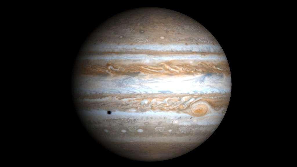 La planète Jupiter photographiée par la sonde Cassini. L'ombre portée sur la géante par l'une de ses lunes est visible en bas à gauche. © Nasa