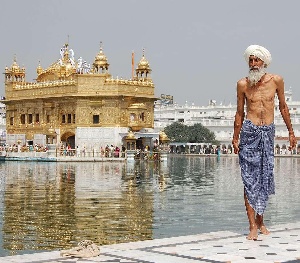 Pèlerin sikh au Temple d'Or à Amritsar, au Pendjab, dans le nord de l'Inde. L'homme à l'avant-plan vient de prendre un bain rituel. © Paulrudd, Wikimedia Commons, GNU 1.2
