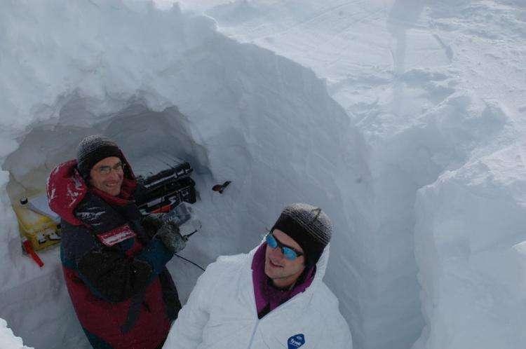 Florent Domine et Samuel Morin effectuent des mesures physiques et des échantillonnages de neige dans un puits creusé dans un glacier du Spitzberg. © LGGE
