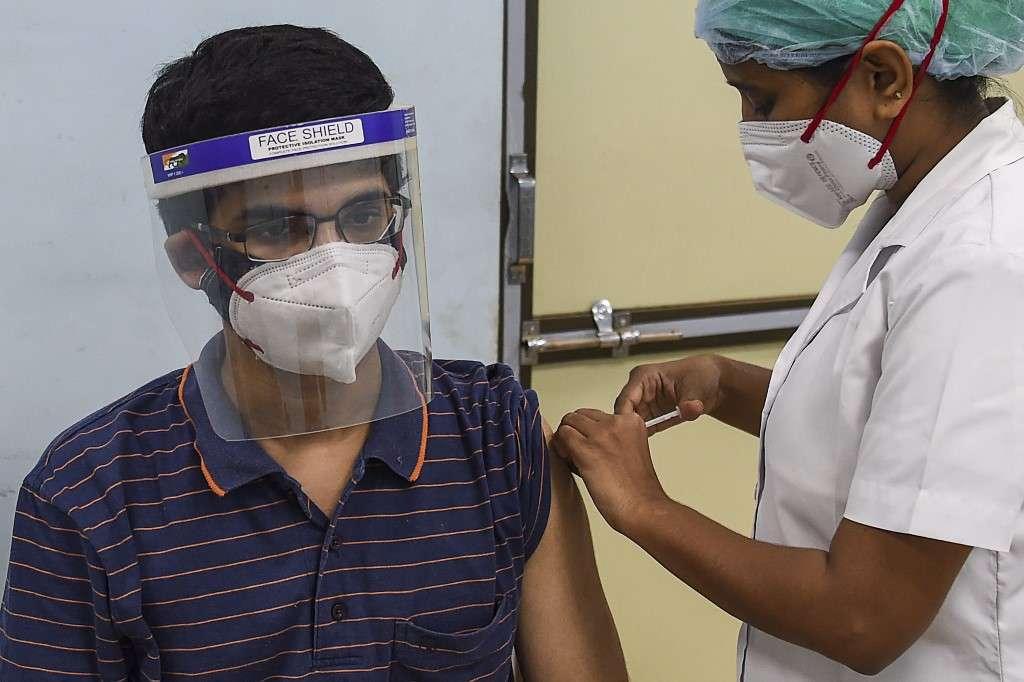 Un agent de santé inocule à un étudiant une dose du vaccin contre le coronavirus Covid-19 d'AstraZeneca-Oxford à l'hôpital Rajawadi de Mumbai, le 22 juin 2021. © Punit Paranjpe, AFP