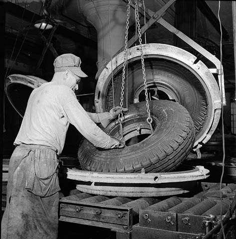 Cet ouvrier de l'usine Société Polymer Limitée (Kitchener, Canada) retire un pneu en caoutchouc synthétique du four de vulcanisation, en octobre 1943. © BiobliArchives/LibraryArchives, Flickr, cc by 2.0