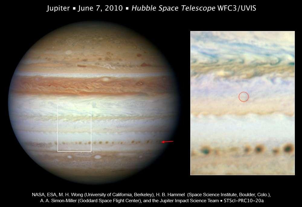 Cette image prise le 7 juin 2010 par le télescope spatial Hubble est venue confirmer qu'aucune cicatrice sombre n'était observable à l'endroit où s'était produit le flash lumineux quatre jours plus tôt (cercle rouge à droite). Un chapelet de taches sombres (flèche rouge) révèle le début de la désagrégation de la couche de nuages blancs qui masquent la bande équatoriale sud. Crédit Nasa/Esa
