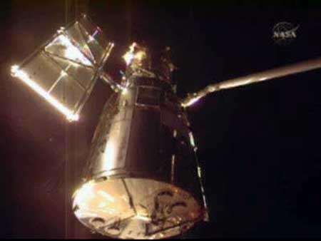 Le télescope spatial vient d'être saisi par le bras manipulateur Canadarm de la navette Atlantis. Capture d'image NasaTV