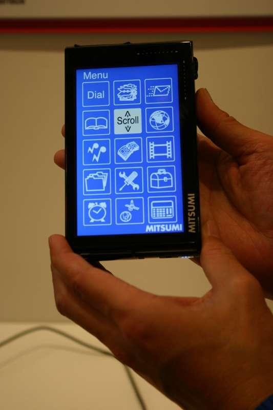 La mauvaise démonstration : le prototype, avec son écran tactile, est présenté avec deux mains alors que sa raison d'être est justement d'être utilisable avec une seule. © Mitsumi