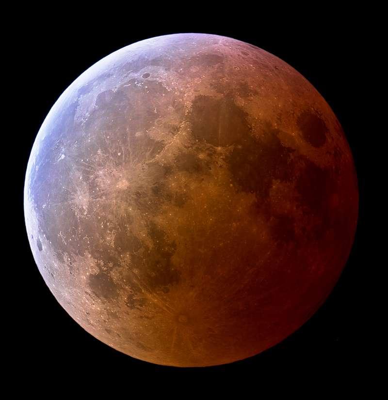 Les poussières dans l'atmosphère terrestre teintent en rouge sombre le cône d'ombre de notre Planète que reflète ici (à droite) la surface de la Lune, au cours de l'éclipse de mars 2007. L'autre moitié commence à y entrer. La couche d'ozone dans la haute atmosphère laisse une empreinte bleu clair, turquoise, visible à gauche. © Jens Hackman, Nasa