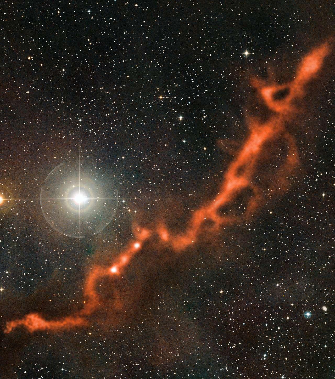 Long de 10 années-lumière, ce filament sinueux de poussière cosmique dans la constellation du Taureau s'est déjà fragmenté pour démarrer le processus de formation stellaire. © ESO/Apex (MPIfR/ESO/OSO)/A. Hacar et al./Digitized Sky Survey 2/Davide De Martin