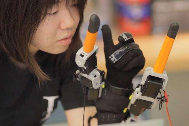 Ce gant développé par le MIT ajoute deux doigts robotisés aux cinq doigts pour pouvoir accomplir des tâches qui nécessitent généralement les deux mains. Il est doté de capteurs qui détectent la position des doigts humains et relaient l'information à un algorithme qui va synchroniser les doigts artificiels. © Melanie Gonick, Massachusetts Institute of Technology