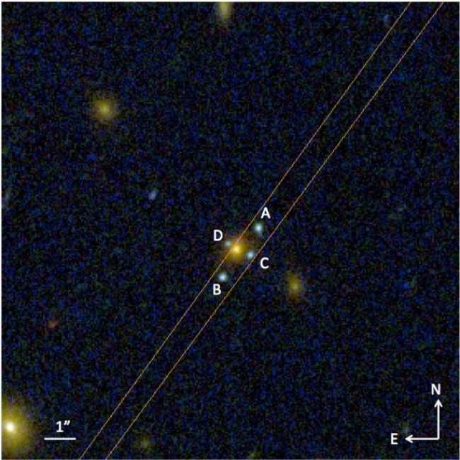 La croix d'Einstein J2211-0350 vue par Hubble. La galaxie elliptique au premier plan (en jaune, au centre) démultiplie l'image d'une source lumineuse encore plus éloignée, ici une autre galaxie, et forme quatre images (en bleu, notées A, B, C et D) disposées en croix autour d'elle. © Hubble Space Telescope