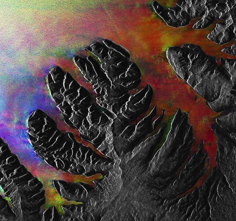 Cette image étrange, en fausses couleurs, est en fait la combinaison de trois photos prises par Envisat, au-dessus des fjords islandais. Les terres apparaissent grises tandis que l'eau arbore une livrée multicolore. © Esa