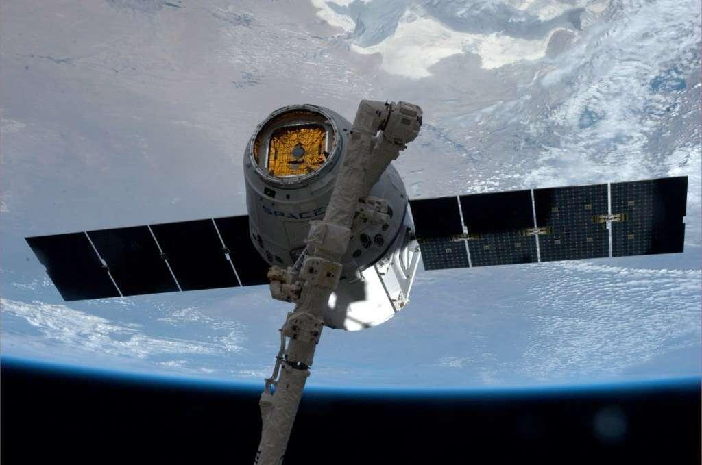 Saisie par le bras robotique de la Station spatiale internationale, la capsule Dragon de SpaceX est amarrée au module Harmony de la partie états-unienne de l'ISS. © Nasa