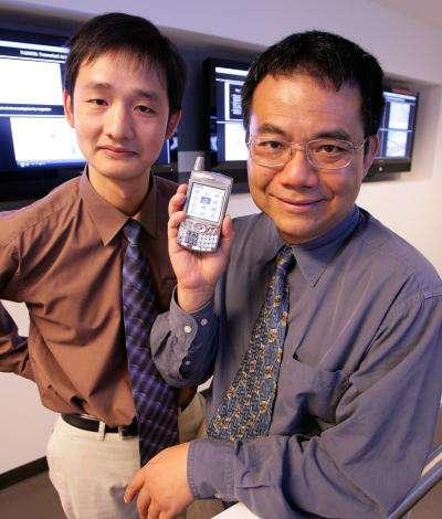 Yang Yang, à droite, et Jinsong Huang, à gauche, montrent un téléphone mobile. Ils en sont sûrs : dans peu de temps, les fabricants de ce genre d'appareils se seront convertis aux écrans Pled. Crédit : UCLA Engineering/R. Hutchinson