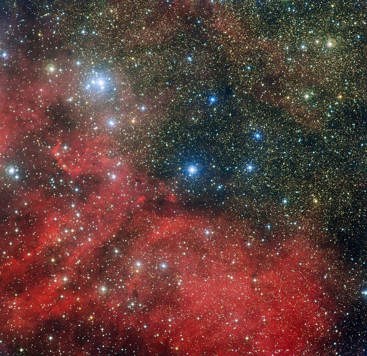 L'amas d'étoiles NGC 6604 est dévoilé sur cette nouvelle image prise avec la caméra WFI installée sur le télescope MPG/ESO de 2,2 mètres de l'Observatoire La Silla au Chili. NGC 6604 est le groupement lumineux qui s'étend en haut à gauche de l'image. C'est un jeune amas d'étoiles qui constitue la partie la plus dense d'un groupe plus largement étendu contenant environ une centaine d'étoiles bleuâtres lumineuses. L'image montre également la nébuleuse associée à cet amas – un nuage d'hydrogène ionisé lumineux appelé Sh2-54 – ainsi que des nuages de poussière. © ESO