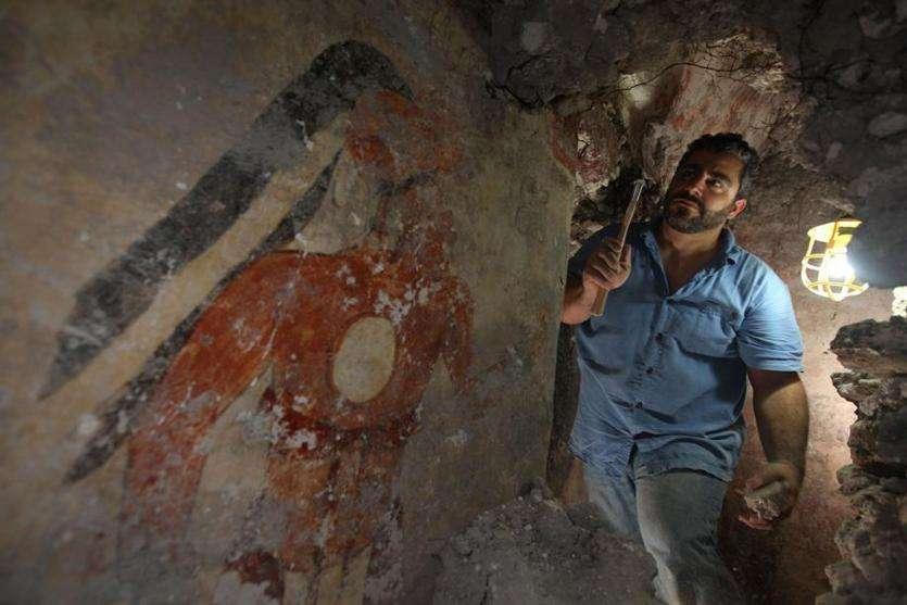 William Saturno, archéologue à l'université de Boston, devant l'une des peintures murales datant du IXe siècle découvertes dans les ruines du site maya de Xultun au Guatemala. La fouille et la préservation du site ont été prises en charge par la National Geographic Society. © Tyrone Turner/2012 National Geographic