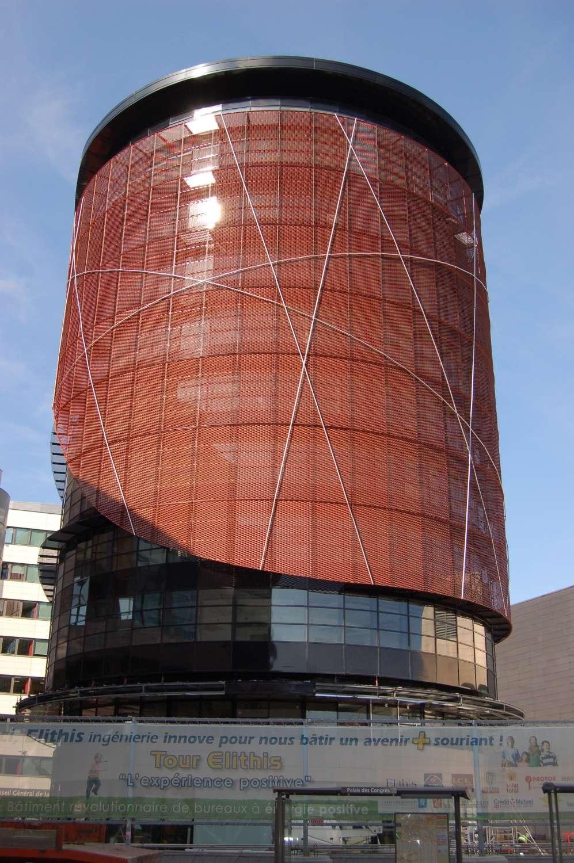 La tour Elithis, à Dijon, un immeuble de bureaux dit à énergie positive. Un ensemble de techniques (notamment le treillage métallique visible sur cette photographie, filtrant les rayons du soleil quand il est haut dans le ciel) réduisent fortement la consommation énergétique. © Elithis