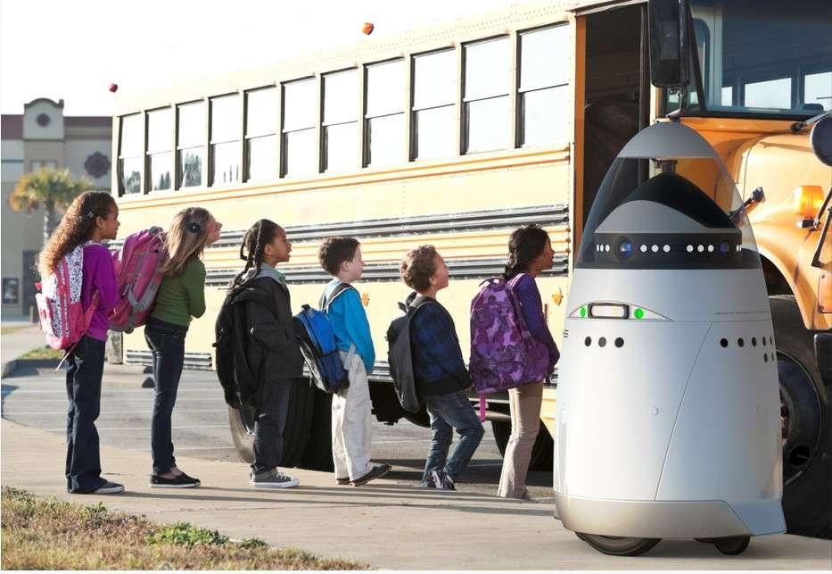 Un robot K5 surveillant des élèves prenant leur bus scolaire. Grâce à son système de reconnaissance faciale, il pourrait s'assurer de la présence de chaque enfant à l'arrivée et au départ, et déclencher une alerte en cas de problème. Terminée l'école buissonnière ! © Knightscope