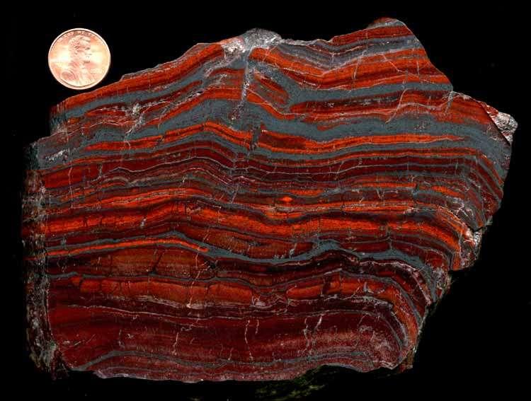 Un échantillon de roche provenant d'un gisement de fer rubané. Le penny en haut à gauche mesure 19 mm de diamètre. © Michael Vanden Berg