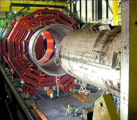 Assemblage du CMS. Le détecteur à muons est visible en périphérie, le noyau central (avant-plan) comprenant le solénoïde supraconducteur et le trajectographe, entre autres.