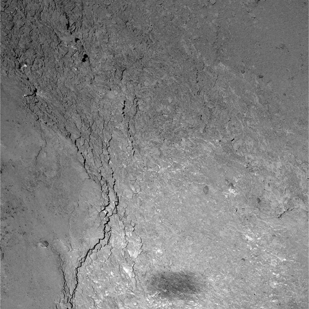 Dans cette aire de 228 x 228 m couverte par la caméra à angle étroit, petit champ (Nac) de l'instrument Osiris à bord de Rosetta, on distingue de magnifiques détails de la surface de la comète 67P/Churyumov-Gerasimenko, capturés lors du survol du 14 février, à 6 km d'altitude. En bas de l'image, on aperçoit l'ombre grossière de Rosetta qui s'étend sur quelque 20 x 50 m. La résolution est de 11 cm par pixel. Téléchargez l'image en haute résolution ici. © Esa, Rosetta, MPS for Osiris Team, MPS, UPD, Lam, IAA, SSO, Inta, UPM, DASP, Ida
