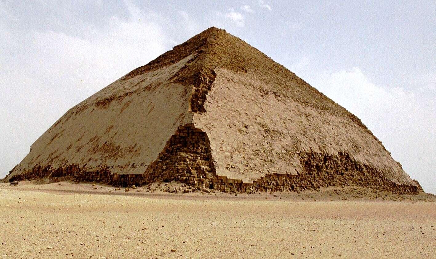 La célèbre pyramide rhomboïdale, au sud-ouest de Memphis et à environ 10 km au sud de Saqqarah, doit ce surnom à sa forme, avec une moitié supérieure moins pentue que la base. La première pyramide élevée par le pharaon Snéfrou sur le site de Dahchour doit sans doute cette caractéristique à un problème durant sa construction. À mi-chemin, ses bâtisseurs ont dû craindre que la pyramide ne s'effondre sous son propre poids. © Wikipédia, CC BY-SA 2.5
