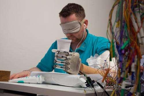 Dennis Aabo Sørensen testant la nouvelle main robotisée. Il raconte que grâce à elle, il peut ressentir la forme et la texture de différents objets. © École polytechnique fédérale de Lausanne