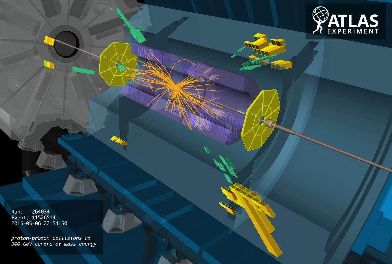 Le 6 mai 2015, des collisions de protons se sont à nouveau produites dans le détecteur Atlas du LHC. Les trajectoires des nouvelles particules chargées issues des collisions à 0,9 TeV ont été reconstituées par les ordinateurs (en orange sur l'image). Elles sont courbées par des champs magnétiques. Les énergies déposées sont indiquées en vert et jaune. © ATLAS Collaboration, Cern