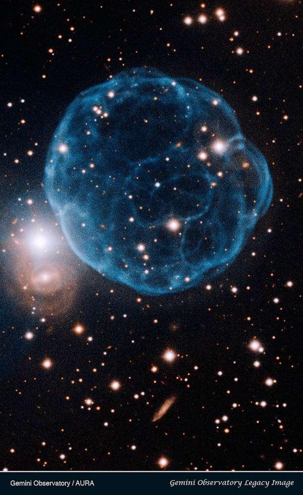 Kronberger 61 est une coquille de gaz ionisé qui ressemble à un ballon de football. La naine blanche qui en est à l'origine est l'étoile bleue près du centre. © Gemini Observatory/Aura