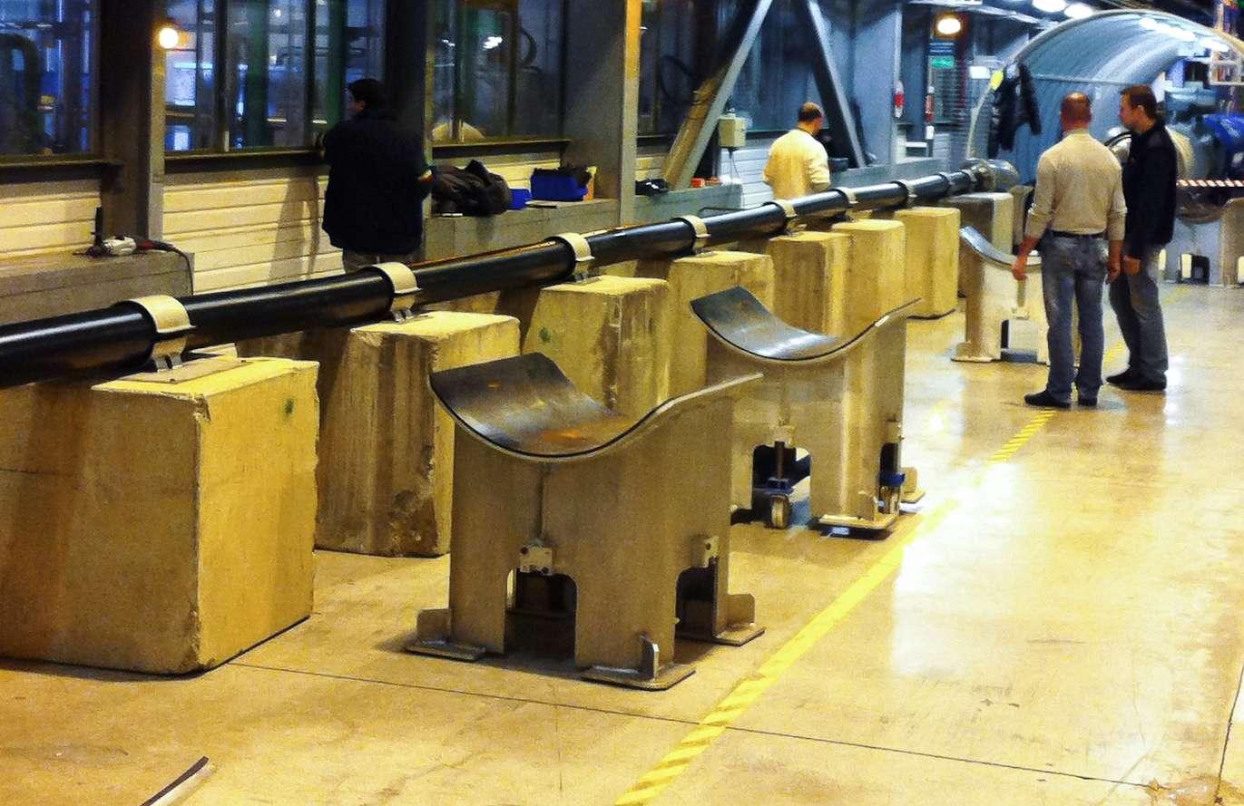 Le tube noir est le cryostat semi-flexible qui assurera le refroidissement des câbles MgB2 du tunnel du LHC jusqu'à la surface où se trouveront les alimentations électriques des aimants supraconducteurs du HL-LHC. Ce cryostat mesure 20 m de long pour un diamètre d'environ 16 cm. © Cern