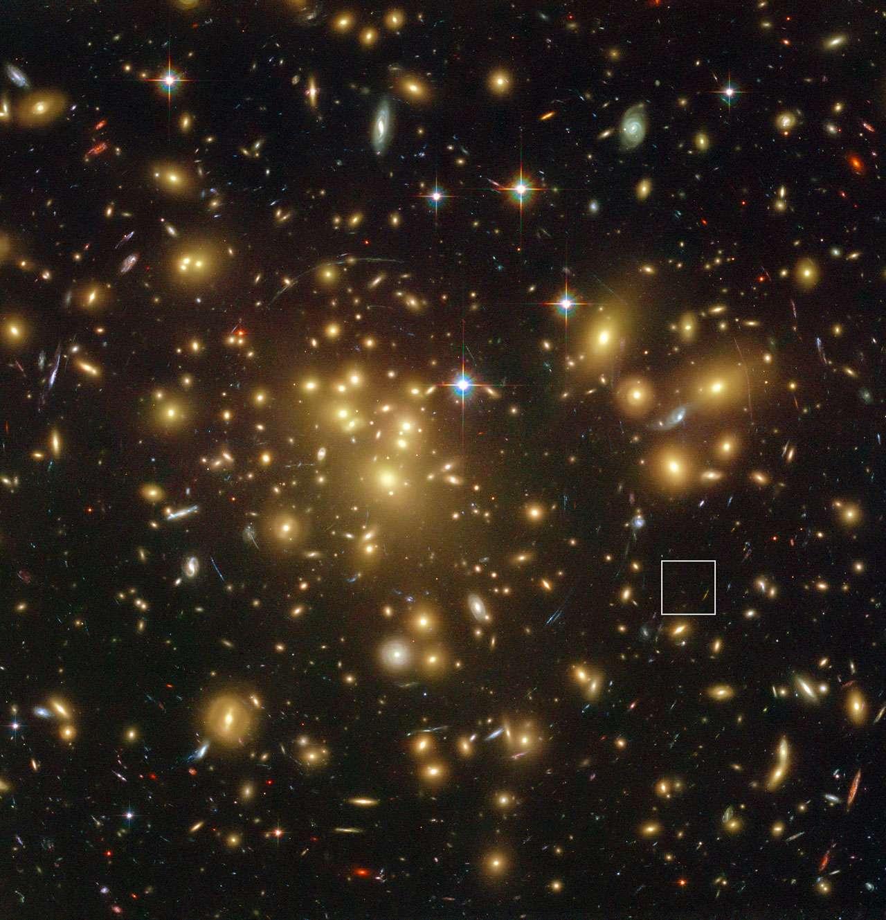 L'immense et massif amas de galaxies Abell 1689 photographié par Hubble. La lumière d'objets plus distants est déviée par l'énorme concentration de galaxies, ce qui peut augmenter leur luminosité au point de les rendre visibles comme dans le cas de l'objet A1689-zD1 (encadrement à droite). Sa luminosité a été amplifiée d'un facteur 9. Son décalage vers le rouge (redshift) est de 7,5. © Nasa, Esa, L. Bradley et H. Ford (Johns Hopkins University), R. Bouwens et G. Illingworth (University of California)