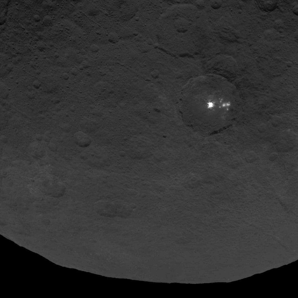 Au moins huit autres points brillants jouxtent la grande surface blanche et très réfléchissante située dans ce cratère de 90 km de diamètre. La résolution de cette image prise par la sonde Dawn le 9 juin 2015 est de 410 mètres par pixel. © Nasa, JPL-Caltech, UCLA, MPS, DLR, IDA