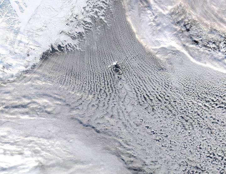 Une image prise par l'instrument Modis (Moderate Resolution Imaging Spectroradiometer), installé sur les satellites de la Nasa, Aqua et Terra. Elle montre, en vraies couleurs, une région de l'Atlantique au nord de l'Islande, autour de l'île Jan Mayen, visible au centre. On voit nettement des nuages formant des structures linéaires (les « rues de nuages »). C'est là qu'ont lieu les échanges de chaleur et d'humidité entre la mer et l'atmosphère : cette région est celle de l'Amoc (Atlantic Meridional Overturning Circulation), un mécanisme climatique qui apporte de la chaleur sur l'Europe. © GWK Moore