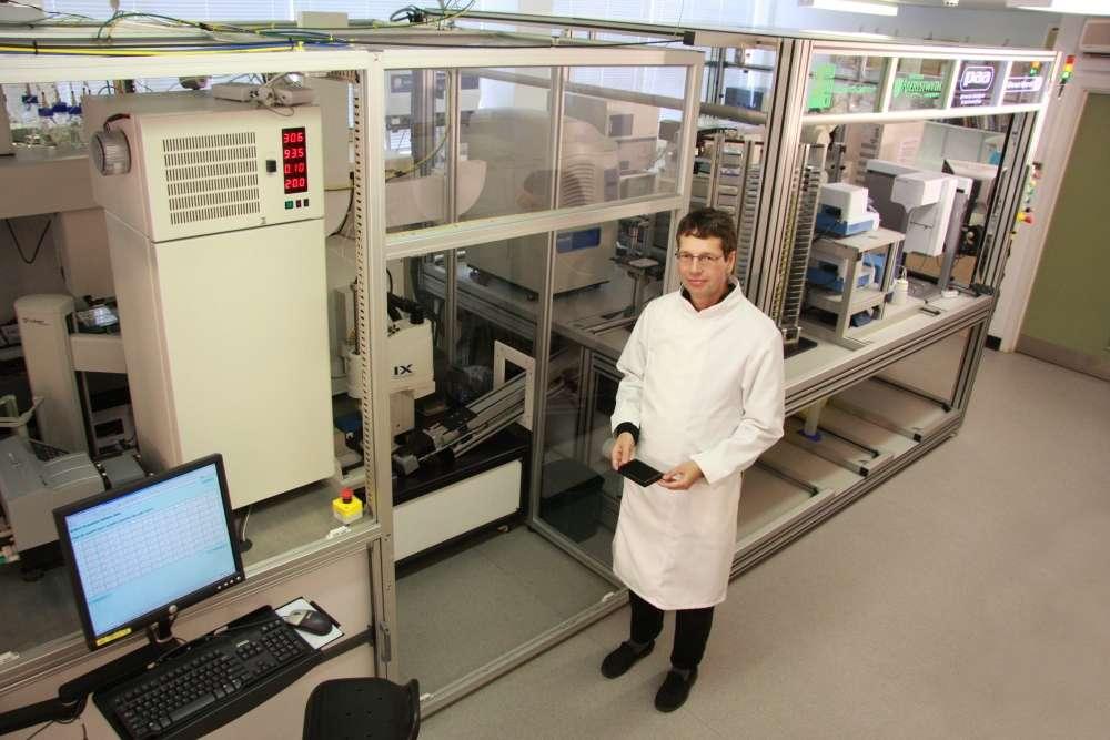A droite, Ross King. Derrière lui, Adam, qui occupe une pièce entière. A gauche, l'écran d'un des quatre ordinateurs qui constituent la partie purement informatique du robot scientifique. © 2005 - 2009, Aberystwyth University
