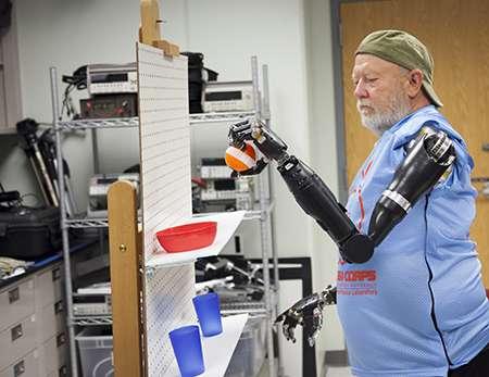 Amputé des deux bras, Les Baugh déplace un objet en contrôlant ses prothèses par la pensée. © Johns Hopkins University Applied Physics Laboratory