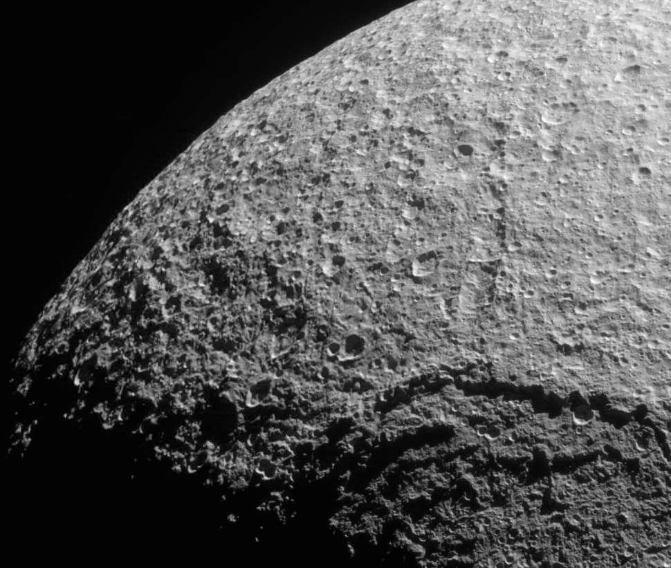 Vue de la surface cratérisée du satellite Téthys. On distingue le bord du cratère Odyssée, résultat d'un violent impact qui s'est produit dans la jeunesse du satellite. © Nasa/JPL/Space Science Institute
