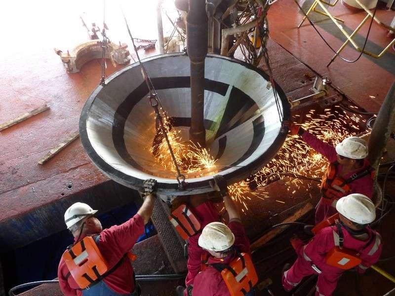 Le cône d'entrée du futur puits de carottage est assemblé sur le bateau JOIDES Resolution puis descendu par la « moon pool ». © Jean-Luc Berenguer