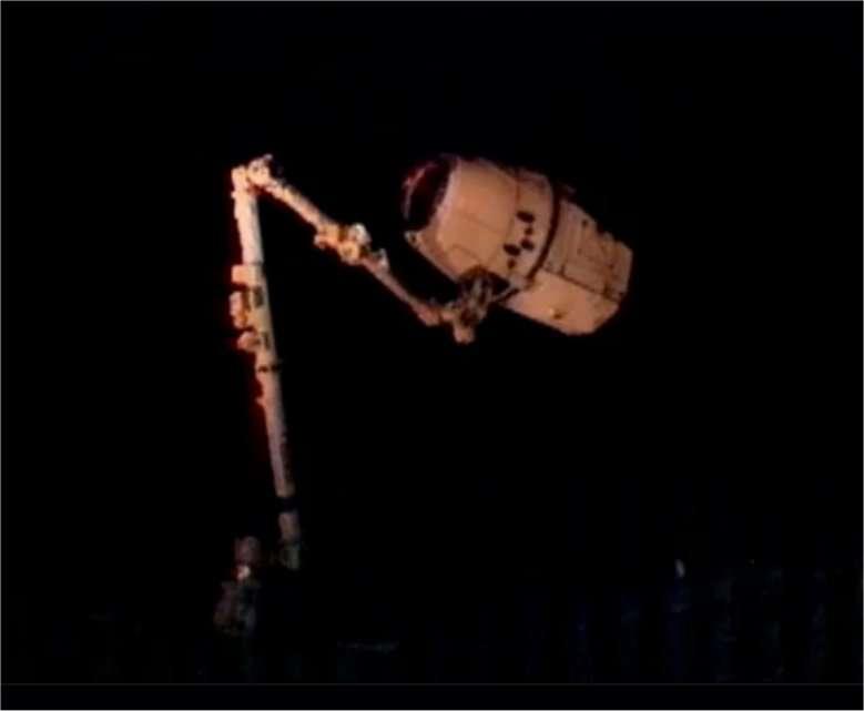 Le cliché est médiocre mais historique : la capsule Dragon, ce vendredi 25 mai 2012 à 14 h 04 TU, construite par l'entreprise SpaceX, fondée par Elon Musk, vient d'être agrippée par le bras de la Station spatiale internationale. L'ère de l'après-navette a vraiment commencé. © Nasa