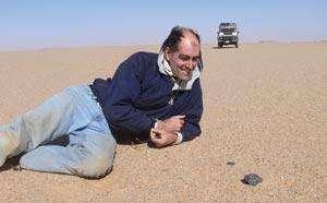 Peter Jenniskens pose devant un morceau de 2008 TC3, bien noir sur le sable du Sahara. © Peter Jenniskens