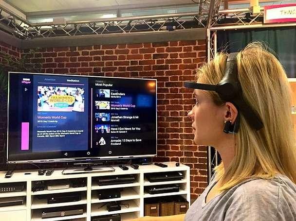 La chaîne britannique BBC a mis au point un prototype de système de contrôle par la pensée pour remplacer la télécommande du téléviseur. Muni d'un casque EEG, la personne concentre son attention sur l'application et le programme qu'elle souhaite visionner. © BBC