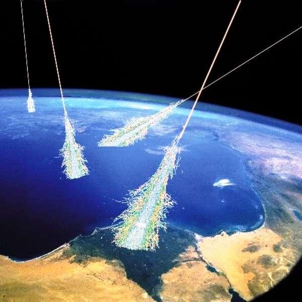 Une représentation d'artiste sur fond d'une photo de la Nasa montrant la chute de rayons cosmiques sur Terre. Les particules des rayons cosmiques en heurtant les noyaux de la haute atmosphère génèrent des gerbes de particules secondaires. © Simon Swordy (U. Chicago), NASA