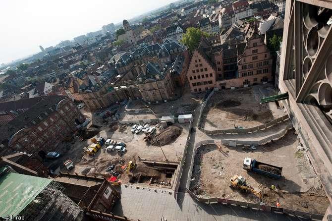 Vue panoramique des bâtiments entourant la place du Château à Strasbourg, en 2012. Le cliché est pris depuis la cathédrale, vers le sud. Au premier plan, l'opération archéologique ; à l'arrière-plan, sur la gauche, l'avancée d'un suivi de réseau. © Inrap