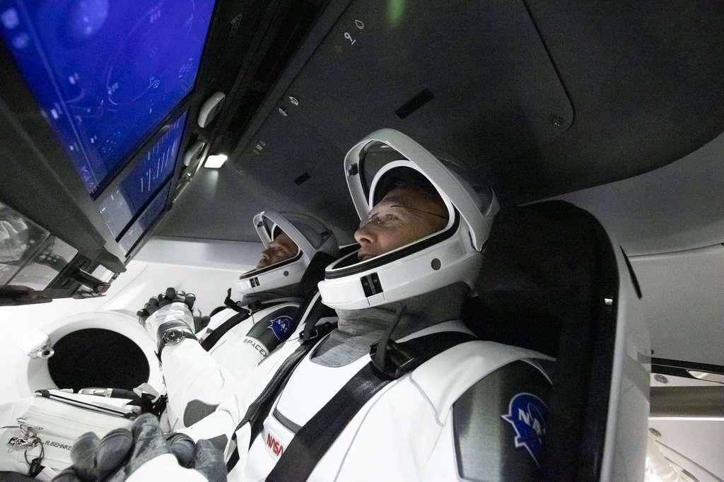 Les astronautes Bob Behnken et Doug Hurley, à bord du Crew Dragon et son cockpit futuriste, devront attendre quelques jours de plus avant de décoller à destination de la Station spatiale internationale. © SpaceX, Nasa