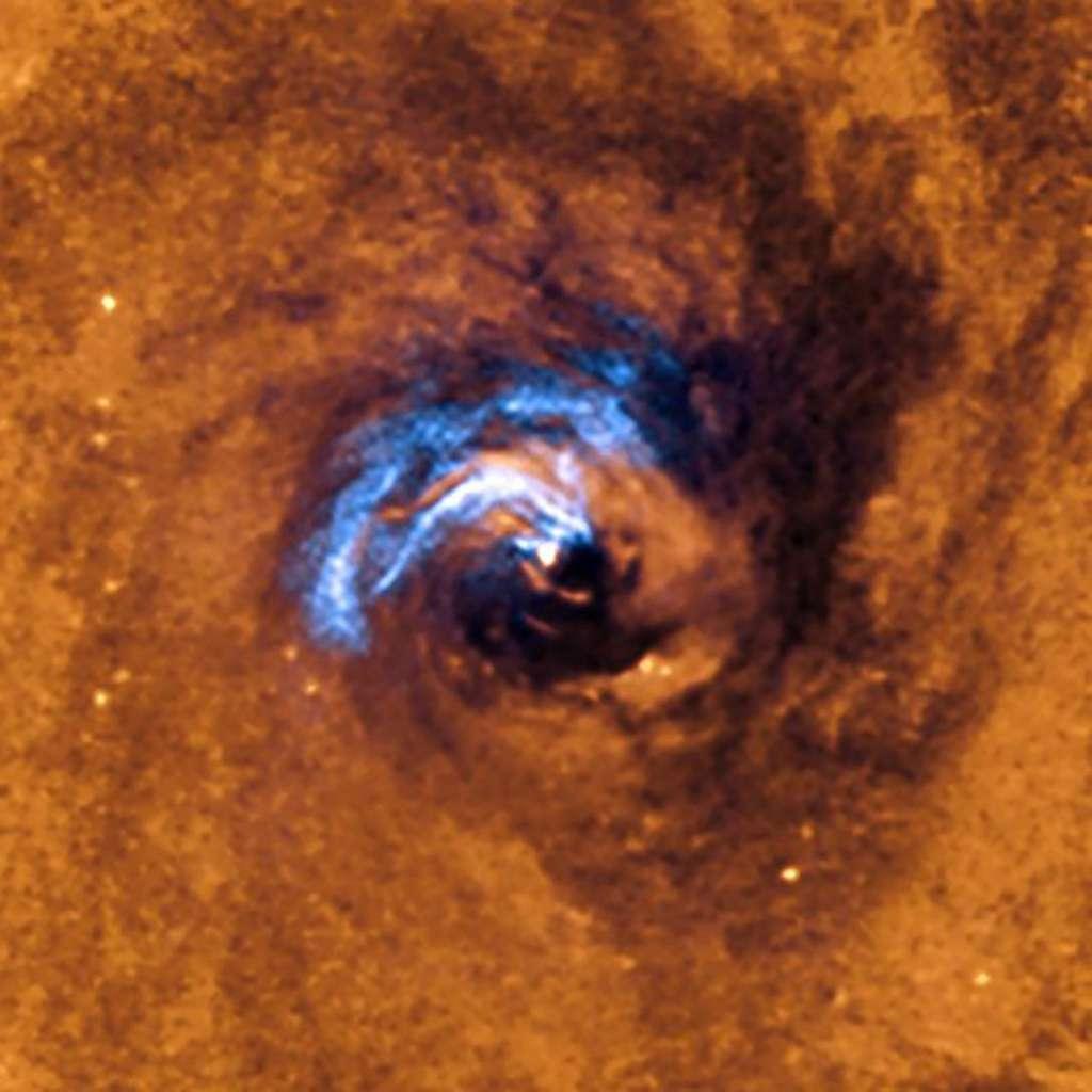 Processus d'ingestion de filaments de poussière par le trou noir supermassif de NGC 1566. © ESO, IAC