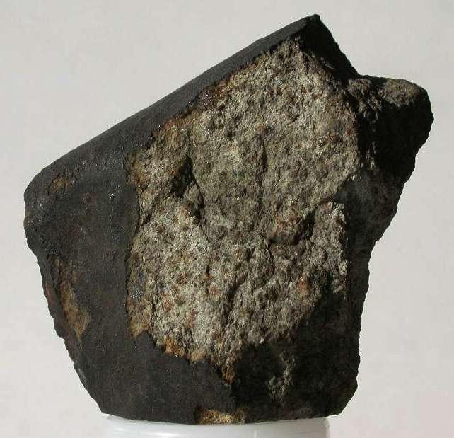 La météorite pierreuse (ou chondrite) de High Possil en Écosse, serait représentative de la constitution du manteau, selon Edouard Roche. Le fragment ci-dessus pèse 151 g. L'assemblage, constitué d'olivine et de pyroxènes (teintes vertes), est entouré d'une croûte noire, verre résultant de la fusion de la surface de l'aérolithe lors de son entrée dans l'atmosphère. © The Hunterian, université de Glasgow, 2012