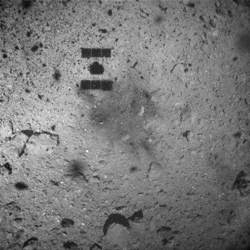 Image de la surface de Ryugu capturée une minute après le touchdown du 22 février 2019 (heure du Japon) par l'Optical Navigation Camera - Wide Angle (ONC-W1) de Hayabusa-2. La sonde était alors à environ 25 m d'altitude. Une tache est visible sur le sol à côté de son ombre. Cette décoloration de la surface provient peut-être de la matière soufflée par les propulseurs de Hayabusa-2 ou par l'impact de son projectile. © Jaxa, University of Tokyo, Kochi University, Rikkyo University, Nagoya University, Chiba Institute of Technology, Meiji University, University of Aizu, AIST