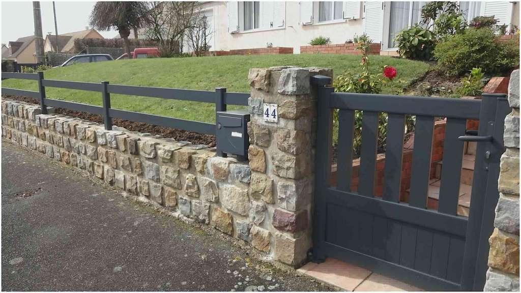Clôture en aluminium sur mur-bahut en pierre naturelle, hourdée au mortier, réalisé en soutènement d'un jardin en pente. © Lapeyre
