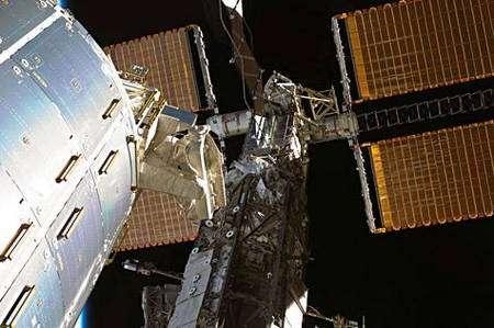 Troisième sortie. Steve Bowen et Heidemarie Stefanyshyn-Piper (cette dernière étant hors cadre) concentrent leurs efforts sur le SARJ dont ils achèvent le remplacement de quatre des douze roulements à billes. Remarquez, là aussi, la disproportion entre l'astronaute (au centre de l'image) et l'immense structure.