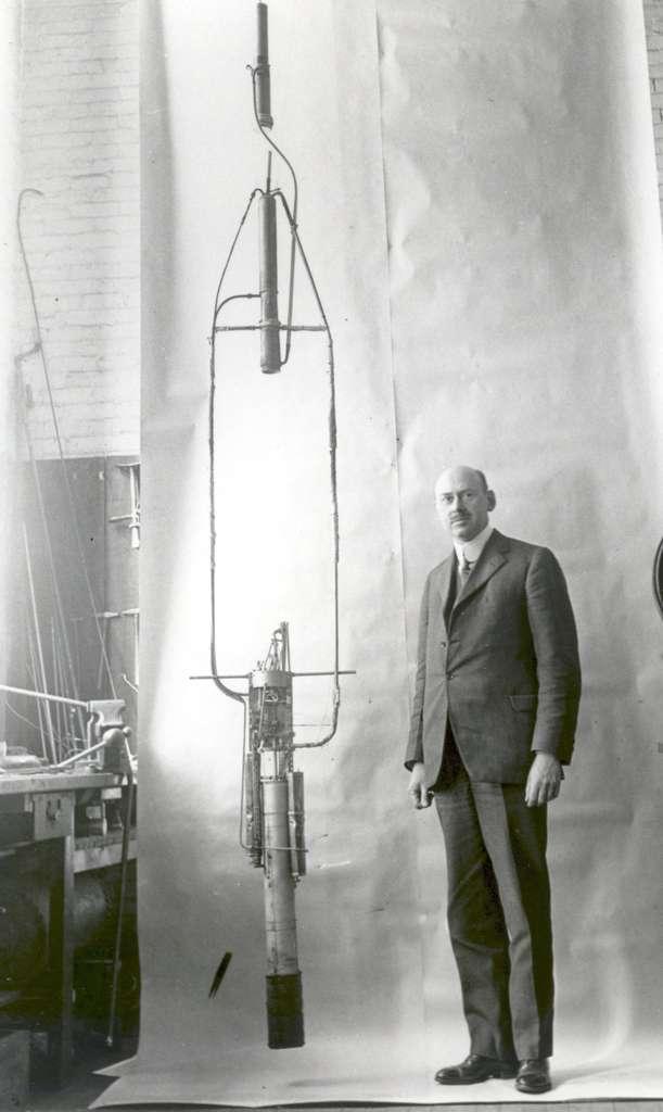 Robert Goddard pose devant sa fusée à propergols liquides en 1925. Le propulseur est dans la partie supérieure et les réservoirs et les pompes sont installés en bas. Dans l'esprit de l'inventeur, cette disposition devait améliorer la stabilité. © Nasa